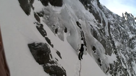 A screenshot from the helmet cam video. I have just completed the traverse across the snow ramp, and I am placing an ice screw to protect the belay before launching onto the ice.