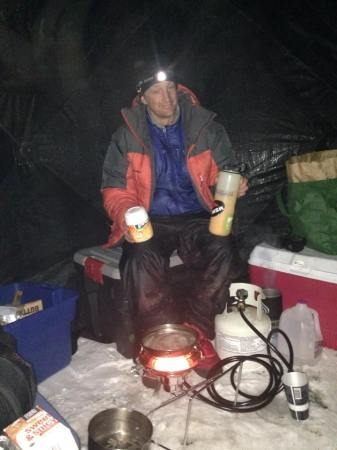 Olin mixing Tang and frying sausages for dinner in our propane-heated ice house.